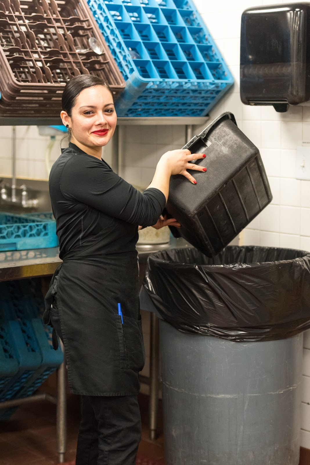 a female restaurant worker dumping food remains in the garbage